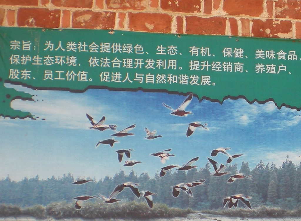 "A poster from the Wang family farm, which reads: ""Provide human society with green, ecological, organic, healthful, delicious food … Promote the harmonious development of humanity and nature."""