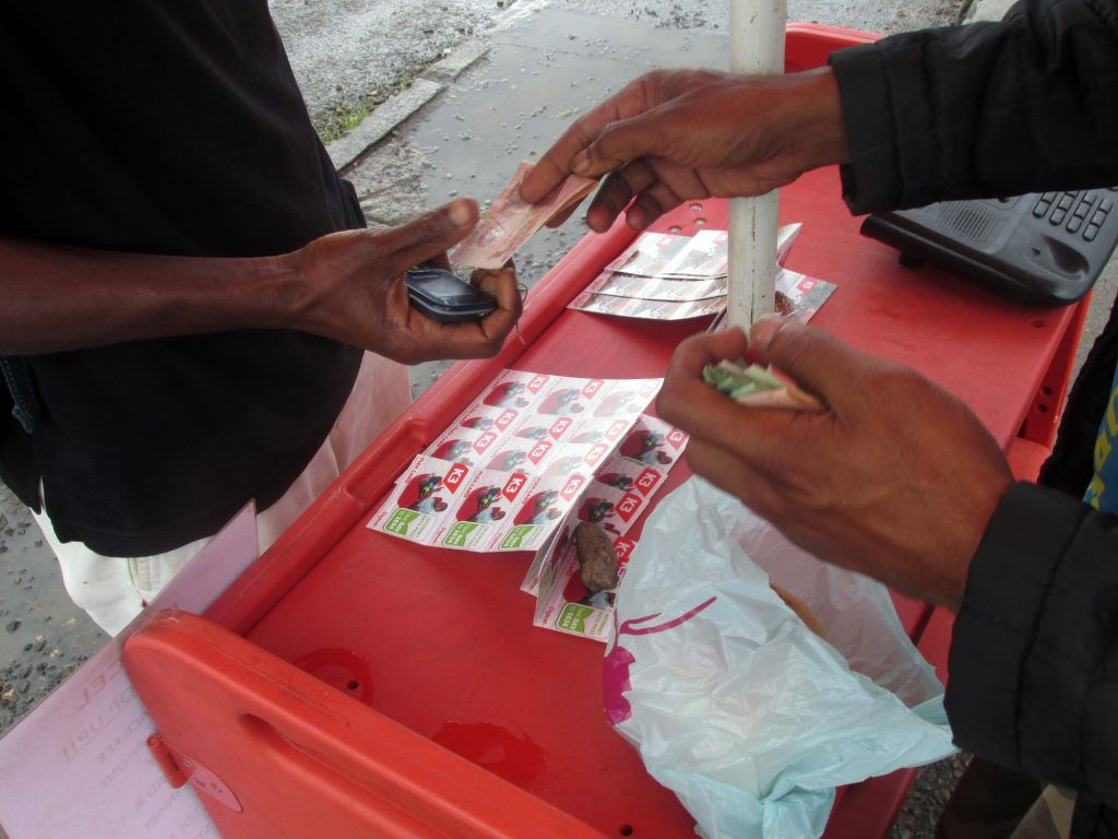 "Street vendor selling scratch or ""flex"" cards, Goroka, 2015"