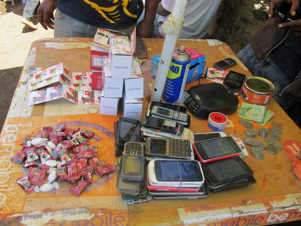 Phone repair vendor's table, Goroka, 2015