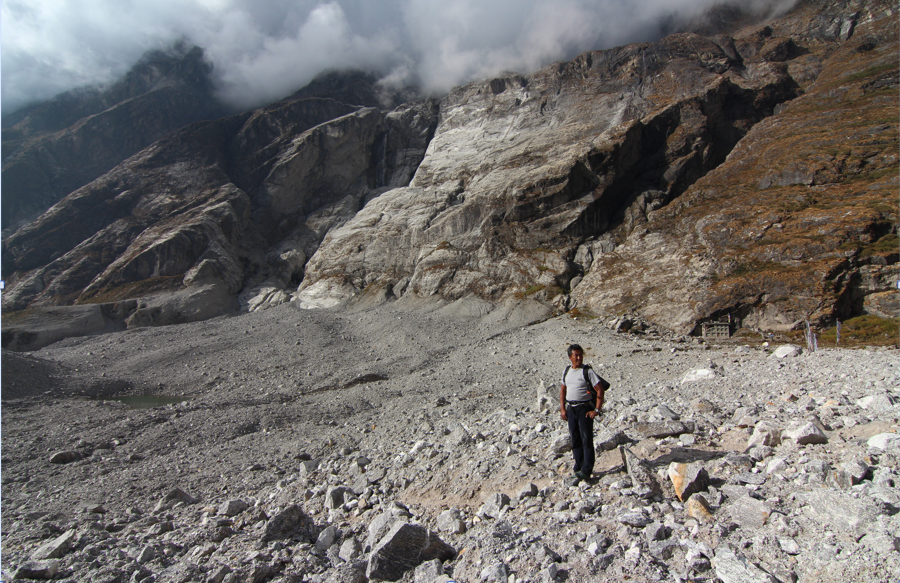 Figure 15. Dindu, the man who I was speaking with about the proposed hydropower project at the time of the earthquake, stands in the blast zone of the Langtang avalanche (Austin Lord).