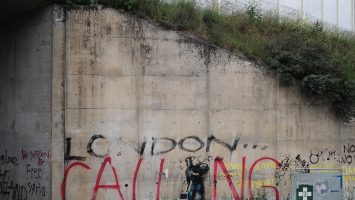 "Figure 1. Bansky mural depicting Steve Jobs as a migrant defaced with ""London Calling"" graffiti. (Leleu)"