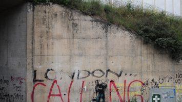 "Figure 1. Bansky mural depicting Steve Jobs as a migrant defaced with ""London Calling"" graffiti. (Leleu)"