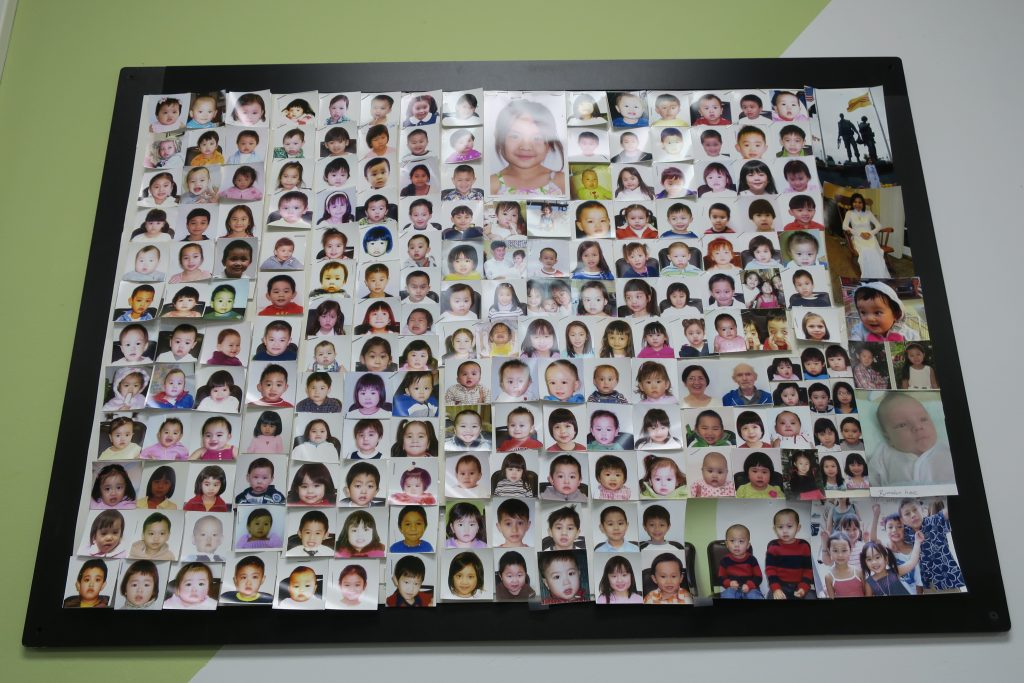 """Wall of customers"" passport photos, Vietnamese American remittance shop."